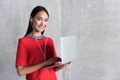 Elegant joyful businesswoman is working on computer. Online communication. Portrait of stylish positive young woman is smiling and holding laptop while standing Royalty Free Stock Images