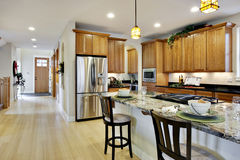 Elegant Kitchen. Elegant, brightly lit kitchen with island and light wood cabinetry Stock Photos