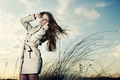 elegant kvinna för modeståenderaincoat Arkivbild