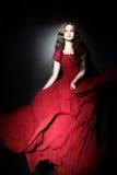 Elegant kvinna i rött mode för lång klänning arkivbilder