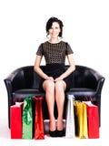 Elegant kvinna i svart klänning med shoppingpåsar. royaltyfria foton