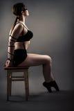 Elegant kvinna med bundna händer som sitter på stol med stängda ögon Royaltyfria Bilder