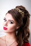 Elegant kvinna med chic smink och frisyr med en krona på hans H royaltyfria bilder
