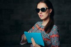 Elegant kvinna med den Retro Cat Eye Sunglasses och kopplinghandväskan Arkivbild