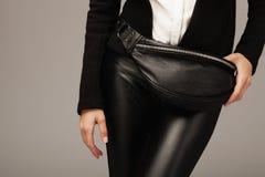 Elegant kvinna med en läderfannypacke Arkivfoton