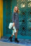 Elegant kvinna nära blå dörr royaltyfri foto