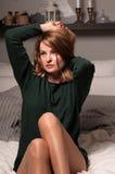 Elegant kvinna på en säng med härliga solbrända ben royaltyfria bilder