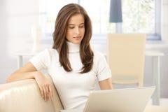 Elegant kvinna på sofaen med bärbar dator royaltyfria bilder