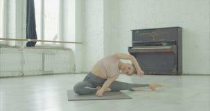 Elegant kvinna som gör kondition som sträcker övningar lager videofilmer