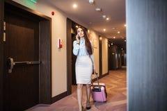 Elegant kvinna som talar på den smarta telefonen, medan lämna hotellet med resväskan arkivbilder