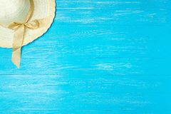Elegant kvinnlig sugrörhatt för ram på blå träbakgrund, copyspace för text, sommarsemester royaltyfria foton
