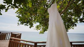 Elegant lace dress of the bride hanging on a tree on the hotel terrace overlooking the ocean. Philippine exotic. Shooting in motion stock video footage