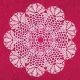 Elegant lacy doily on canvas. Royalty Free Stock Photography