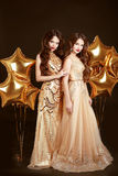 Elegant ladies on party. Beautiful sexy girls wearing in gold fa Royalty Free Stock Photography