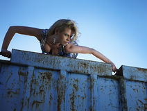 Elegant lady against old rusty container Stock Photography