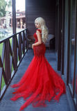 Elegant lady blonde in a red evening dress. Beautiful blonde girl with long hair. The elegant lady is in a luxurious red dress with a long train. Evening make-up royalty free stock image
