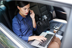 Elegant lady. Elegant business lady sitting in car and working on laptop Stock Photos
