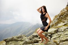 Elegant lady in dress standing on the mountain rocks Stock Images