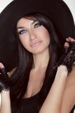 Elegant lady. Fashion brunette woman model posing in black hat i Stock Photos