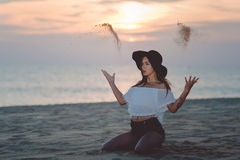 Elegant lady in floppy hat throwing sand sitting. Amazing portrait of beautiful lady wearing black floppy hat sitting on sandy beach and throwing sand in the air Stock Photography