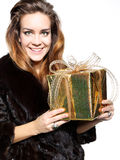 Elegant lady in a fur coat with a gold gift Stock Photos