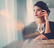 Elegant lady with glass of wine alone in restaurant Stock Image