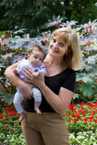 Elegant lady holding a baby in a garden. Elegant lady holding a granddaughter in a garden stock photo