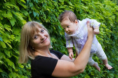 Elegant lady holding a baby in a garden Stock Photos