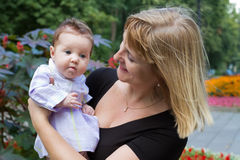 Elegant lady holding a baby in a garden Royalty Free Stock Photography