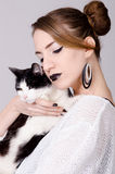 Elegant lady holding black and white cat with yellow eyes Stock Images