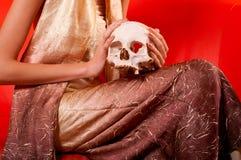 Elegant lady holding human skull Stock Images