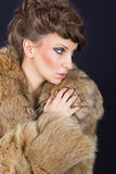 Elegant lady holding red wine glass wearing brown fur coat Royalty Free Stock Photo