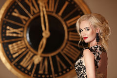 Elegant lady with makeup ang blond hairstyle posing in front of wall clock Royalty Free Stock Images