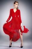 Elegant lady in red dress. Blonde elegant woman in red dress posing in studio , looking at camera. Full photo Royalty Free Stock Images