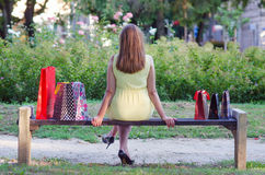 Elegant lady sitting in the park after shopping. On sunny summer day Stock Photography
