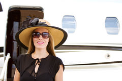 Elegant lady standing by jet plane Stock Images