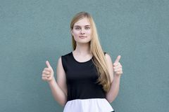 Elegant lady in stylish clothes showing thumbs up royalty free stock image