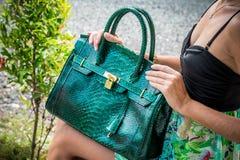Elegant lady with stylish short hairstyle and glasses holding a luxury snake skin python bag. Bali island. Royalty Free Stock Photo