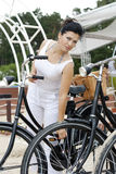 An elegant lady travels on bicycle. An elegant lady in a white clothing travels on a bicycle Royalty Free Stock Photo