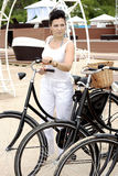 An elegant lady travels on bicycle. An elegant lady in a white clothing travels on a bicycle Royalty Free Stock Images