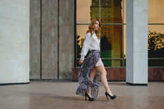 Elegant lady walking alone in the street Stock Images