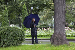Elegant lady walking in a beautiful park under umbrella. On a cold rainy day Royalty Free Stock Photography