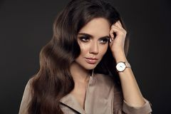 Elegant lady with Watch on hand. Beautiful woman with long healthy wavy hair style posing in studio on dark background stock photo