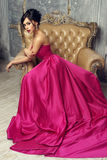 Elegant lady wearing ball gown. Elegant srunning woman sitting in armchair and looking at you. Pretty lady with hairstyle wearing pink ball gown or evening dress Stock Image