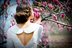 Elegant lady. In a white dress near a tree full of flowers, spring time Royalty Free Stock Photos