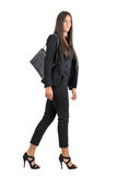 Elegant Latin business female in black suit and handbag walking side view Royalty Free Stock Images