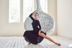 Elegant latin women dancer at hanging chair. Elegant latin woman dancer at hanging chair in clear interior with windows Stock Images