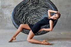 Elegant latin women dancer at hanging chair. Elegant latin woman dancer at hanging chair in grunge interior Royalty Free Stock Photography
