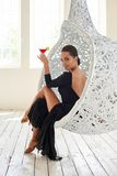 Elegant latin women dancer at hanging chair. Elegant latin woman dancer at hanging chair in clear interior with windows Royalty Free Stock Images