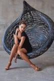 Elegant latin women dancer at hanging chair. Elegant latin woman dancer at hanging chair in grunge interior Royalty Free Stock Images